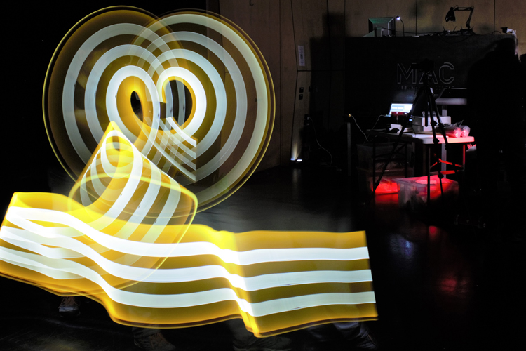 A trail of yellow and white light makes shapes in a dark room.