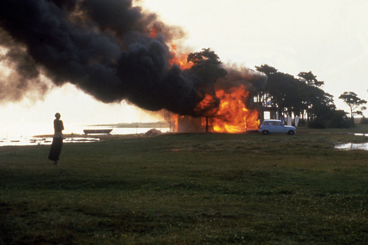 A figure watches a large fire with billowing smoke